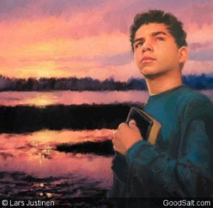 A teenage boy holding his bible with sunset behind him