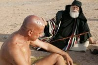 Naked man in desert sitting with friend
