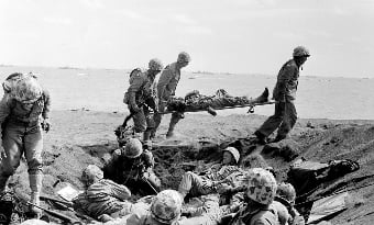 U.S. Corpsmen carry a wounded Marine on a stretcher to an evacuation boat on the beach at Iwo Jima while other Marines huddle in a foxhole during the invasion of the Japanese Volcano Island stronghold in this file photo of Feb. 25, 1945.