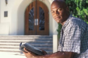 Black man holding Bible in front of church.