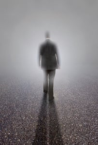 The silhouette of a man in a business suit headed towards a white light.