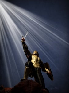 Warrior in golden armor with sword raised in victory, his foot on a defeated demon. Light shines down from heaven.