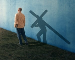 A man walking with his shadow carrying the cross