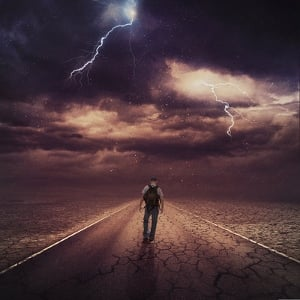 A man walking down a dark road.