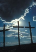 Three crosses silhouetted by blue sky and clouds.