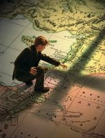 Young Man Standing on Big Map